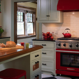 Medium sized eclectic enclosed kitchen in Minneapolis with a submerged sink, flat-panel cabinets, green cabinets, soapstone worktops, beige splashback, ceramic splashback, coloured appliances, lino flooring, multi-coloured floors and black worktops.
