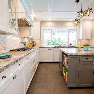 Exempel på ett avskilt, mellanstort klassiskt u-kök, med en undermonterad diskho, luckor med infälld panel, vita skåp, granitbänkskiva, vitt stänkskydd, stänkskydd i marmor, rostfria vitvaror, klinkergolv i porslin, en köksö och grått golv