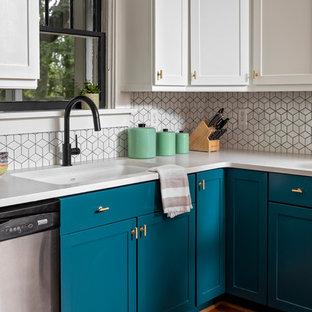 Modern kitchen in Atlanta with recessed-panel cabinets, turquoise cabinets, white splashback, ceramic splashback, light hardwood floors and white benchtop.