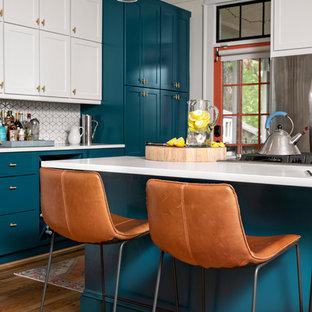 Exemple d'une cuisine moderne avec un placard avec porte à panneau encastré, des portes de placard turquoises, une crédence blanche, une crédence en carreau de céramique, un sol en bois clair et un plan de travail blanc.