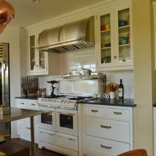 サンタバーバラの中サイズのカントリー風おしゃれなキッチン (シェーカースタイル扉のキャビネット、白いキャビネット、人工大理石カウンター、白いキッチンパネル、サブウェイタイルのキッチンパネル、白い調理設備、濃色無垢フローリング、茶色い床) の写真
