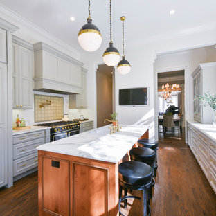 Mid-sized traditional kitchen designs - Example of a mid-sized classic galley medium tone wood floor and brown floor kitchen design in San Francisco with an undermount sink, gray cabinets, quartzite countertops, white backsplash, subway tile backsplash, black appliances, an island, white countertops and recessed-panel cabinets