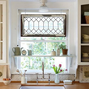 Inredning av ett lantligt mellanstort u-kök, med en rustik diskho, träbänkskiva och vitt stänkskydd