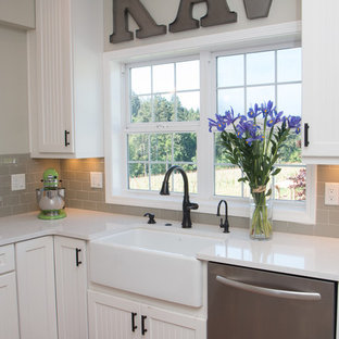 Large country u-shaped separate kitchen in Portland with a farmhouse sink, grey splashback, stainless steel appliances, a peninsula, louvered cabinets, white cabinets, quartz benchtops, ceramic splashback, vinyl floors and brown floor.