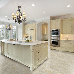 Inspiration for a large traditional l-shaped eat-in kitchen in Miami with raised-panel cabinets, white splashback, subway tile splashback, stainless steel appliances, vinyl floors, with island, beige cabinets and marble benchtops.