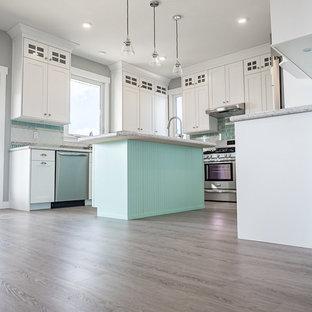 Mittelgroße Shabby-Chic-Style Küche in U-Form mit Doppelwaschbecken, profilierten Schrankfronten, weißen Schränken, Quarzwerkstein-Arbeitsplatte, Küchenrückwand in Grün, Rückwand aus Metrofliesen, Küchengeräten aus Edelstahl, Vinylboden, Kücheninsel und grauem Boden in Edmonton