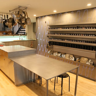 Contemporary l-shaped eat-in kitchen in San Francisco with an undermount sink, flat-panel cabinets, grey cabinets, zinc benchtops, grey splashback, metal splashback, panelled appliances, light hardwood floors, with island, beige floor and grey benchtop.