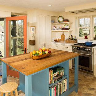 Idéer för att renovera ett mellanstort lantligt kök, med en rustik diskho, luckor med infälld panel, blå skåp, träbänkskiva, rostfria vitvaror, tegelgolv och en köksö