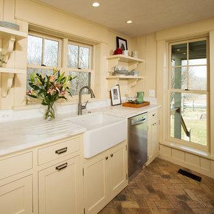 Foto på ett mellanstort lantligt kök, med en rustik diskho, luckor med infälld panel, vita skåp, marmorbänkskiva, rostfria vitvaror, tegelgolv och en köksö