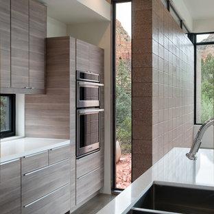 Modern inredning av ett stort kök, med en dubbel diskho, släta luckor, skåp i mellenmörkt trä, bänkskiva i kvarts, rostfria vitvaror, betonggolv och en köksö