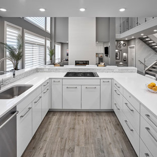 Inspiration for a mid-sized contemporary u-shaped kitchen pantry in Edmonton with an undermount sink, louvered cabinets, white cabinets, quartz benchtops, white splashback, stainless steel appliances, light hardwood floors, with island, brown floor and white benchtop.