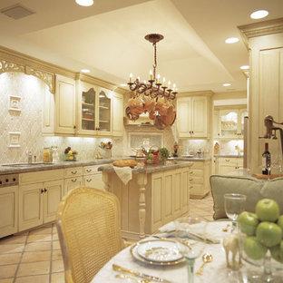 Inspiration för ett stort vintage kök, med en dubbel diskho, luckor med upphöjd panel, gula skåp, granitbänkskiva, vitt stänkskydd, stänkskydd i keramik, integrerade vitvaror, klinkergolv i terrakotta, en köksö och beiget golv