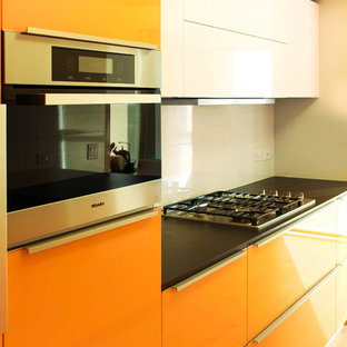 Small modern eat-in kitchen ideas - Inspiration for a small modern single-wall light wood floor eat-in kitchen remodel in Los Angeles with a drop-in sink, flat-panel cabinets, orange cabinets, quartz countertops, black backsplash, porcelain backsplash, stainless steel appliances and no island