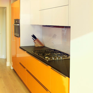 Small modern single-wall eat-in kitchen in Los Angeles with a drop-in sink, flat-panel cabinets, orange cabinets, quartz benchtops, black splashback, porcelain splashback, stainless steel appliances, light hardwood floors and no island.