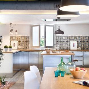 マドリードの大きいインダストリアルスタイルのおしゃれなキッチン (フラットパネル扉のキャビネット、ステンレスキャビネット、木材カウンター、マルチカラーのキッチンパネル、セラミックタイルのキッチンパネル、シルバーの調理設備の、セラミックタイルの床) の写真