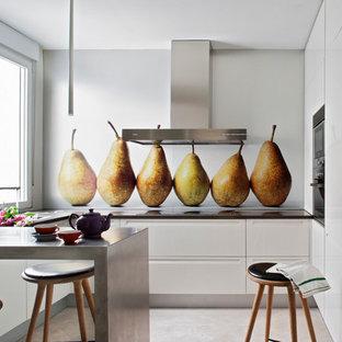 Создайте стильный интерьер: п-образная, отдельная кухня среднего размера в современном стиле с белыми фасадами, столешницей из акрилового камня, полуостровом, плоскими фасадами, разноцветным фартуком, техникой из нержавеющей стали и полом из травертина - последний тренд