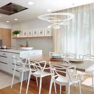 Foto de cocina comedor de galera, contemporánea, grande, con armarios con paneles lisos, puertas de armario blancas, encimera de acrílico, electrodomésticos de acero inoxidable y una isla