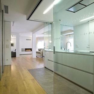 Modelo de cocina contemporánea, abierta, con armarios con paneles lisos y puertas de armario blancas