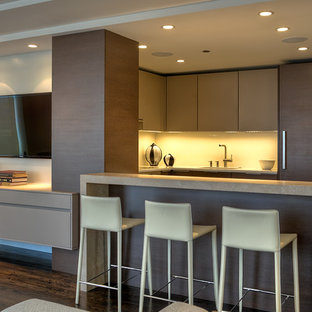 Design ideas for a small modern u-shaped open plan kitchen in Chicago with an undermount sink, flat-panel cabinets, dark wood cabinets, limestone benchtops, white splashback, stainless steel appliances, medium hardwood floors, a peninsula and brown floor.