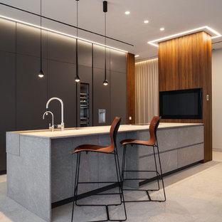 Imagen de cocina de galera, moderna, con fregadero bajoencimera, armarios con paneles lisos, puertas de armario grises, electrodomésticos de acero inoxidable, península, suelo beige y encimeras grises