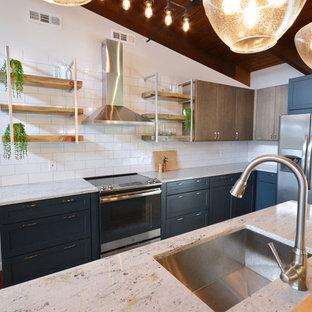 他の地域の中くらいのインダストリアルスタイルのおしゃれなキッチン (アンダーカウンターシンク、フラットパネル扉のキャビネット、青いキャビネット、御影石カウンター、白いキッチンパネル、サブウェイタイルのキッチンパネル、シルバーの調理設備、濃色無垢フローリング、赤い床、白いキッチンカウンター) の写真