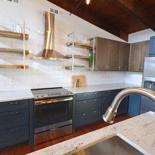 他の地域の中サイズのインダストリアルスタイルのおしゃれなキッチン (アンダーカウンターシンク、フラットパネル扉のキャビネット、青いキャビネット、御影石カウンター、白いキッチンパネル、サブウェイタイルのキッチンパネル、シルバーの調理設備の、濃色無垢フローリング、赤い床、白いキッチンカウンター) の写真