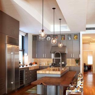 Cette image montre une cuisine design avec un placard à porte plane, des portes de placard grises, une crédence beige, une crédence en dalle de pierre et un électroménager en acier inoxydable.
