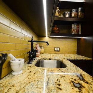 Amerikansk inredning av ett mellanstort flerfärgad linjärt flerfärgat kök med öppen planlösning, med en undermonterad diskho, luckor med infälld panel, skåp i mörkt trä, bänkskiva i kvartsit, gult stänkskydd, stänkskydd i tunnelbanekakel, rostfria vitvaror, klinkergolv i terrakotta, en köksö och orange golv
