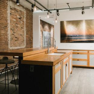 ニューヨークの中サイズのインダストリアルスタイルのおしゃれなキッチン (木材カウンター、アンダーカウンターシンク、落し込みパネル扉のキャビネット、中間色木目調キャビネット、パネルと同色の調理設備、淡色無垢フローリング、グレーの床) の写真