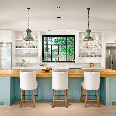 Inspiration for a large coastal u-shaped light wood floor kitchen remodel in Houston with an island, white cabinets, marble countertops, stainless steel appliances, open cabinets, a farmhouse sink, white backsplash and wood backsplash