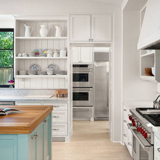 Inspiration for a country l-shaped kitchen in Houston with a farmhouse sink, open cabinets, white cabinets, wood benchtops, white splashback, stone slab splashback, stainless steel appliances, light hardwood floors and with island.
