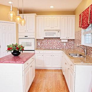 Idee per una cucina a L classica con lavello a doppia vasca, ante con bugna sagomata, ante bianche, top in cemento, paraspruzzi rosso, paraspruzzi con piastrelle a mosaico, elettrodomestici bianchi, pavimento in legno massello medio, isola, pavimento marrone e top rosso