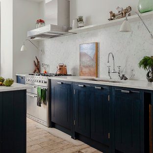 Design ideas for a bohemian kitchen in London with a submerged sink, raised-panel cabinets, black cabinets, white splashback, medium hardwood flooring, an island and marble splashback.
