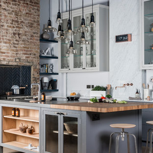 This is an example of a medium sized urban kitchen/diner in London with grey cabinets, marble worktops, grey splashback, stone slab splashback, an island and stainless steel appliances.