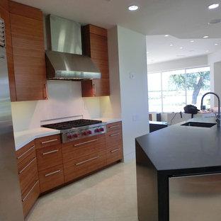ロサンゼルスの広いモダンスタイルのおしゃれなキッチン (ドロップインシンク、フラットパネル扉のキャビネット、淡色木目調キャビネット、人工大理石カウンター、黒いキッチンパネル、石タイルのキッチンパネル、シルバーの調理設備、セラミックタイルの床、ベージュの床) の写真
