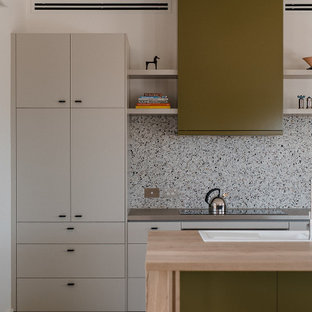 Design ideas for a mid-sized contemporary galley open plan kitchen in Other with a double-bowl sink, flat-panel cabinets, green cabinets, wood benchtops, multi-coloured splashback, porcelain floors, with island, beige floor, brown benchtop and stone slab splashback.