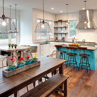 Example of an eclectic dark wood floor kitchen design in Chicago with a farmhouse sink, recessed-panel cabinets, white cabinets, white backsplash, subway tile backsplash, stainless steel appliances and an island