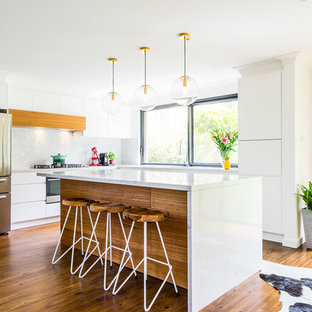 Contemporary l-shaped kitchen in Sydney with an undermount sink, flat-panel cabinets, white cabinets, grey splashback, stainless steel appliances, medium hardwood floors, with island, brown floor and white benchtop.