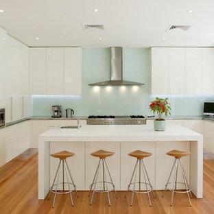 Große Moderne Küche in U-Form mit Unterbauwaschbecken, flächenbündigen Schrankfronten, weißen Schränken, Edelstahl-Arbeitsplatte, Küchenrückwand in Grün, Glasrückwand, Küchengeräten aus Edelstahl, braunem Holzboden und Kücheninsel in Sydney