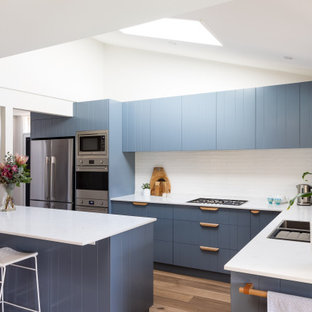 Design ideas for a mid-sized contemporary kitchen with blue cabinets, quartz benchtops, white splashback, porcelain splashback, stainless steel appliances, white benchtop, a double-bowl sink, medium hardwood floors and with island.