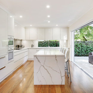 This is an example of a contemporary l-shaped eat-in kitchen in Sydney with an undermount sink, flat-panel cabinets, white cabinets, quartzite benchtops, white splashback, white appliances, medium hardwood floors, with island, brown floor and white benchtop.