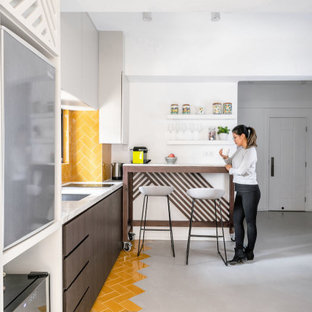 Design ideas for a small asian single-wall open plan kitchen in Hong Kong with an undermount sink, flat-panel cabinets, dark wood cabinets, marble benchtops, yellow splashback, ceramic splashback, stainless steel appliances, ceramic floors, a peninsula, yellow floor and white benchtop.