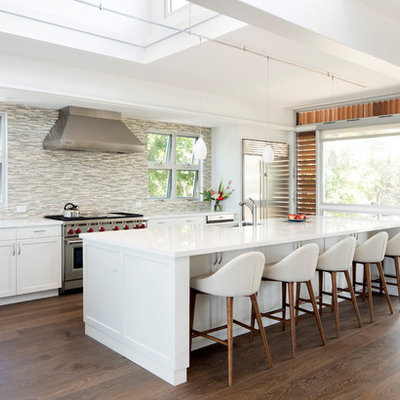 Inspiration for a large tropical l-shaped dark wood floor and brown floor open concept kitchen remodel in Hawaii with an undermount sink, shaker cabinets, white cabinets, multicolored backsplash, matchstick tile backsplash, stainless steel appliances, an island, white countertops and solid surface countertops