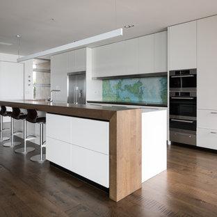 オークランドのコンテンポラリースタイルのおしゃれなキッチン (フラットパネル扉のキャビネット、白いキャビネット、木材カウンター、マルチカラーのキッチンパネル、シルバーの調理設備、無垢フローリング、茶色い床、茶色いキッチンカウンター) の写真