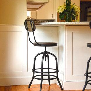 オマハの小さいビーチスタイルのおしゃれなキッチン (エプロンフロントシンク、シェーカースタイル扉のキャビネット、白いキャビネット、クオーツストーンカウンター、マルチカラーのキッチンパネル、ガラスタイルのキッチンパネル、シルバーの調理設備の、無垢フローリング、オレンジの床、グレーのキッチンカウンター) の写真
