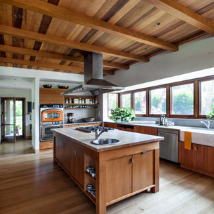 ニューヨークの広いコンテンポラリースタイルのおしゃれなキッチン (エプロンフロントシンク、フラットパネル扉のキャビネット、中間色木目調キャビネット、グレーのキッチンパネル、シルバーの調理設備、淡色無垢フローリング、ベージュの床、板張り天井) の写真