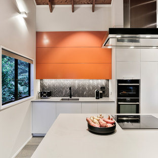 Inspiration for a mid-sized modern galley eat-in kitchen in Auckland with a single-bowl sink, flat-panel cabinets, orange cabinets, quartz benchtops, black splashback, porcelain splashback, black appliances, painted wood floors, with island, grey floor and grey benchtop.