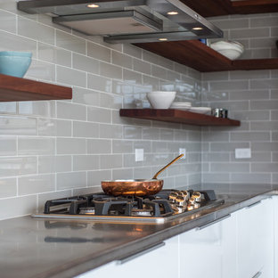 Small modern l-shaped open plan kitchen in Cleveland with an undermount sink, flat-panel cabinets, white cabinets, copper benchtops, grey splashback, porcelain splashback, stainless steel appliances, concrete floors, with island and grey floor.