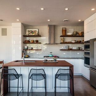 Modelo de cocina en L, moderna, pequeña, abierta, con una isla, fregadero bajoencimera, armarios con paneles lisos, puertas de armario blancas, encimera de cobre, salpicadero verde, salpicadero de azulejos de porcelana, electrodomésticos de acero inoxidable, suelo de cemento y suelo gris