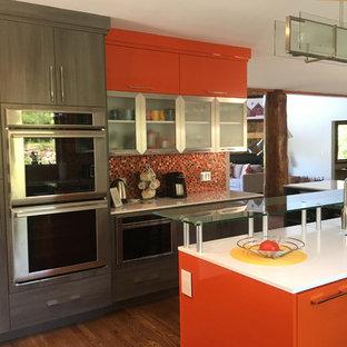 ソルトレイクシティの大きいコンテンポラリースタイルのおしゃれなキッチン (ドロップインシンク、フラットパネル扉のキャビネット、オレンジのキャビネット、珪岩カウンター、マルチカラーのキッチンパネル、セラミックタイルのキッチンパネル、シルバーの調理設備の、無垢フローリング) の写真